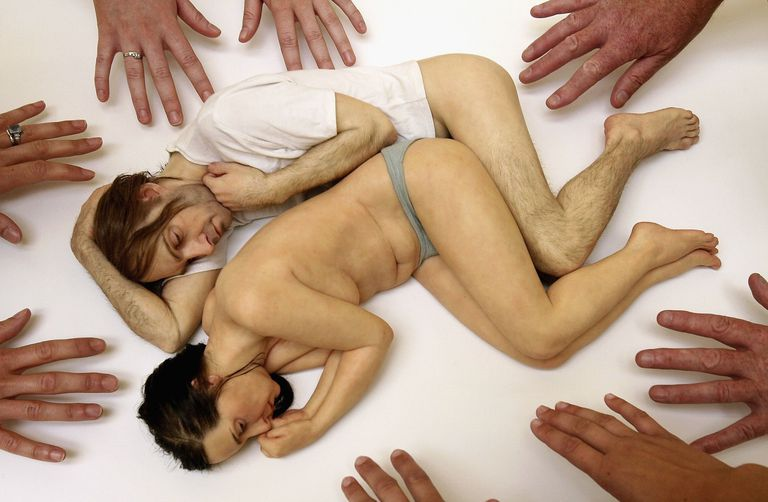 Hands reach torward a realistic sculpture of a miniature sleeping couple
