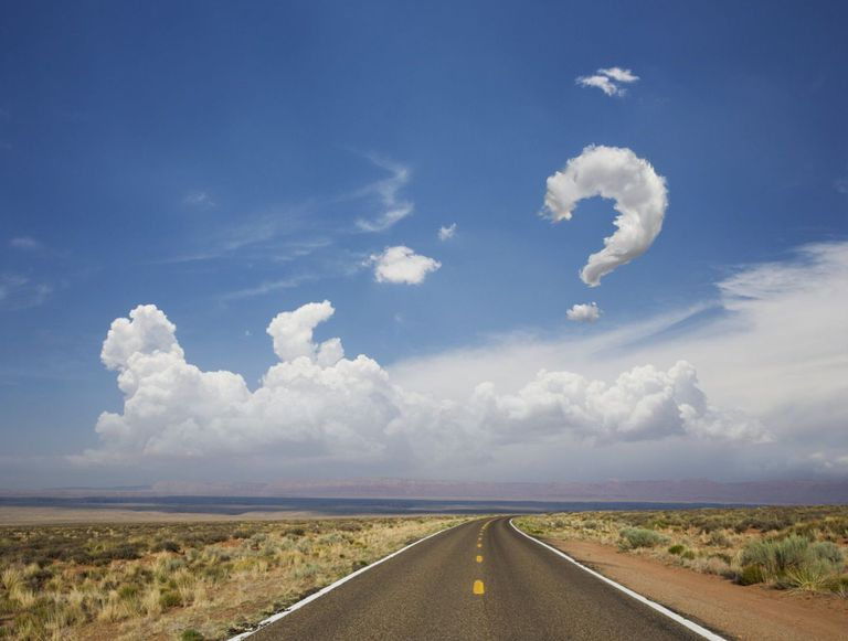 Road in desert with a question mark in the clouds