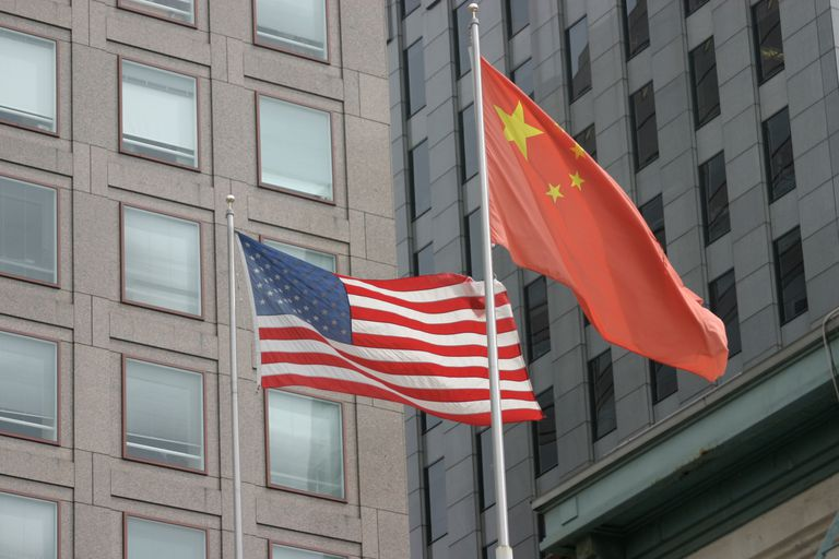Low Angle View Of US and Chinese Flags Against Building In City