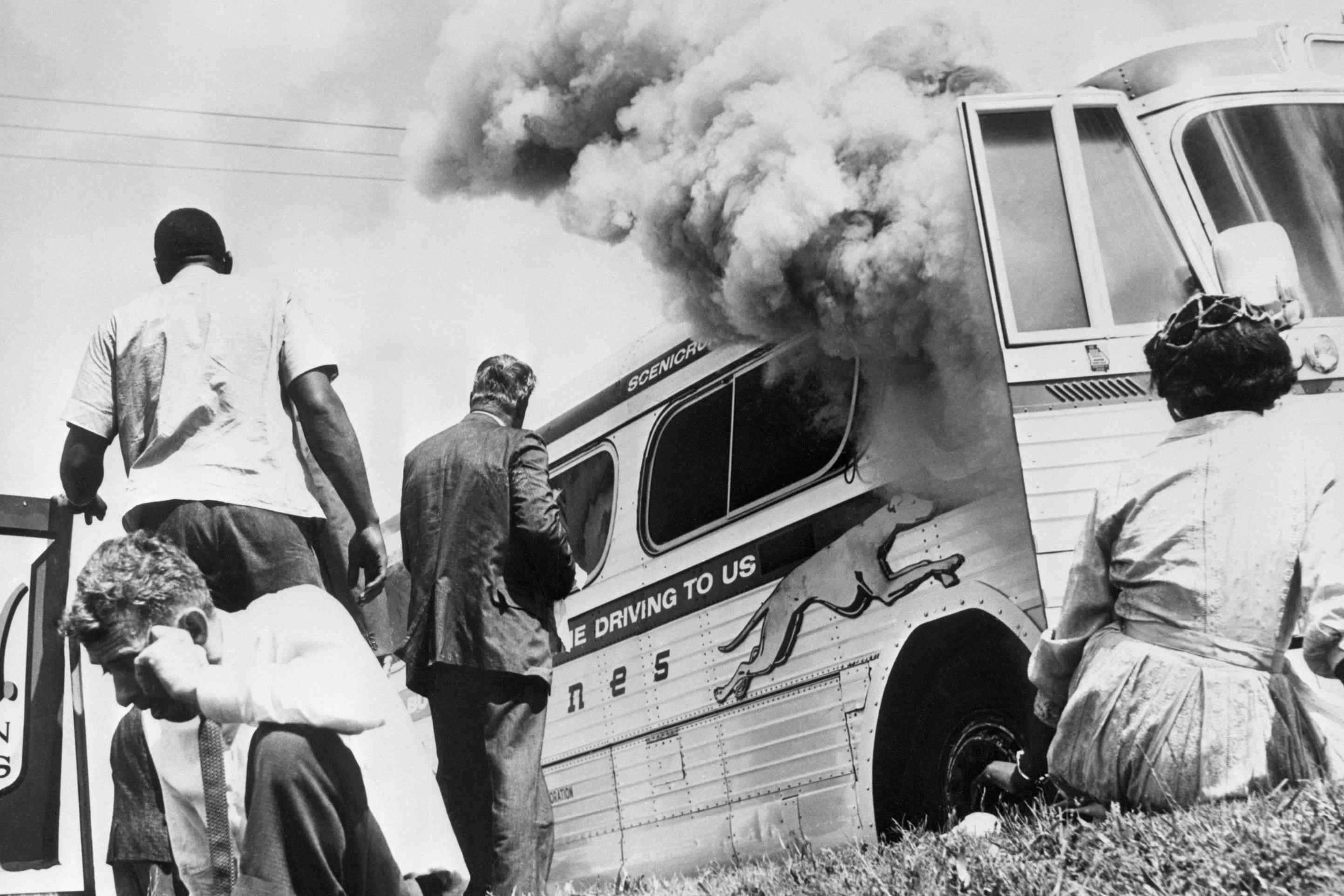 Freedom Riders sit and stand outside of their bus as smoke comes out of the windows