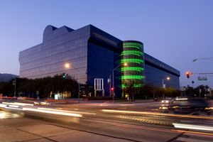 modern glass building with blue glass facade and green spiral protrusion on one side