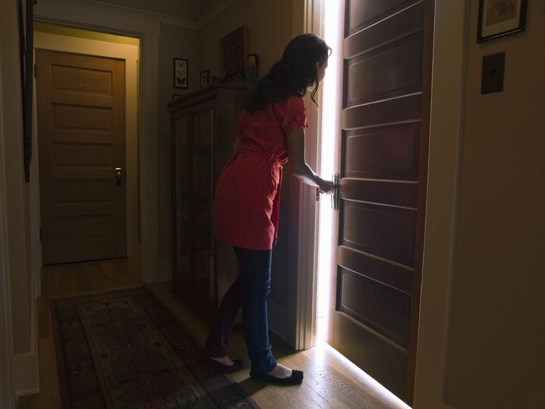 woman opening door to a lit room
