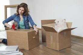 Woman taping up cardboard box
