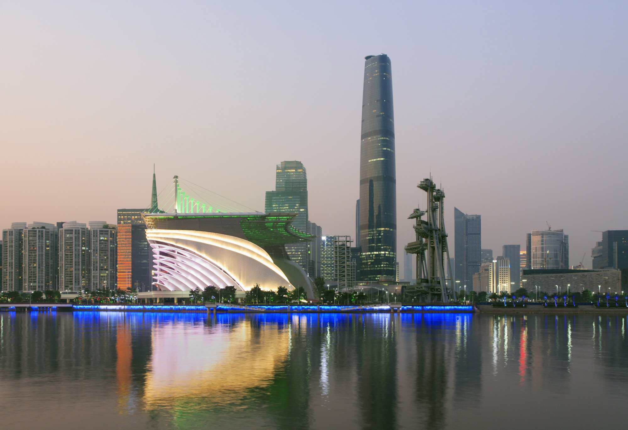 Skyline of Canton, China at dusk, with modern opera house reflecting in river