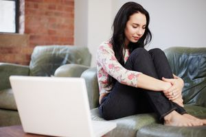 Teen girl curled up crying on a couch with computer in front of her