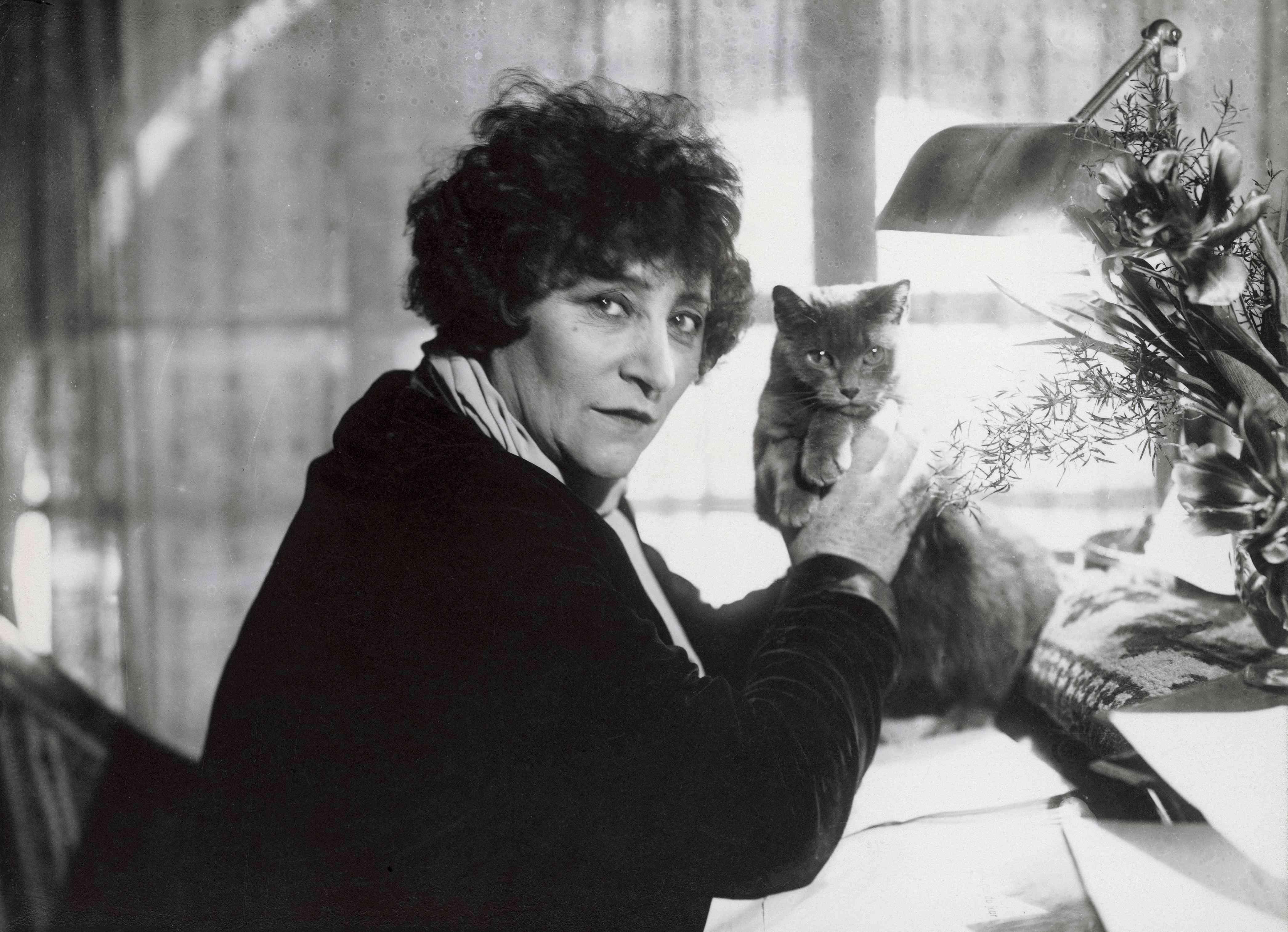 Colette en su escritorio, sosteniendo un gato y mirando a la cámara