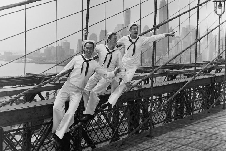 "American actors Jules Munshin, Frank Sinatra and Gene Kelly standing on the Brooklyn Bridge in a still from ""On The Town"""
