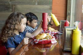 Children having burgers in restaurant