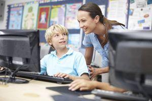 Teacher helping student at a computer