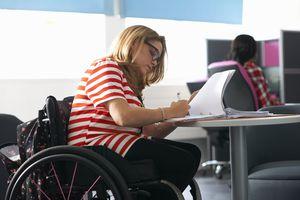 Teenage girl in wheelchair studying