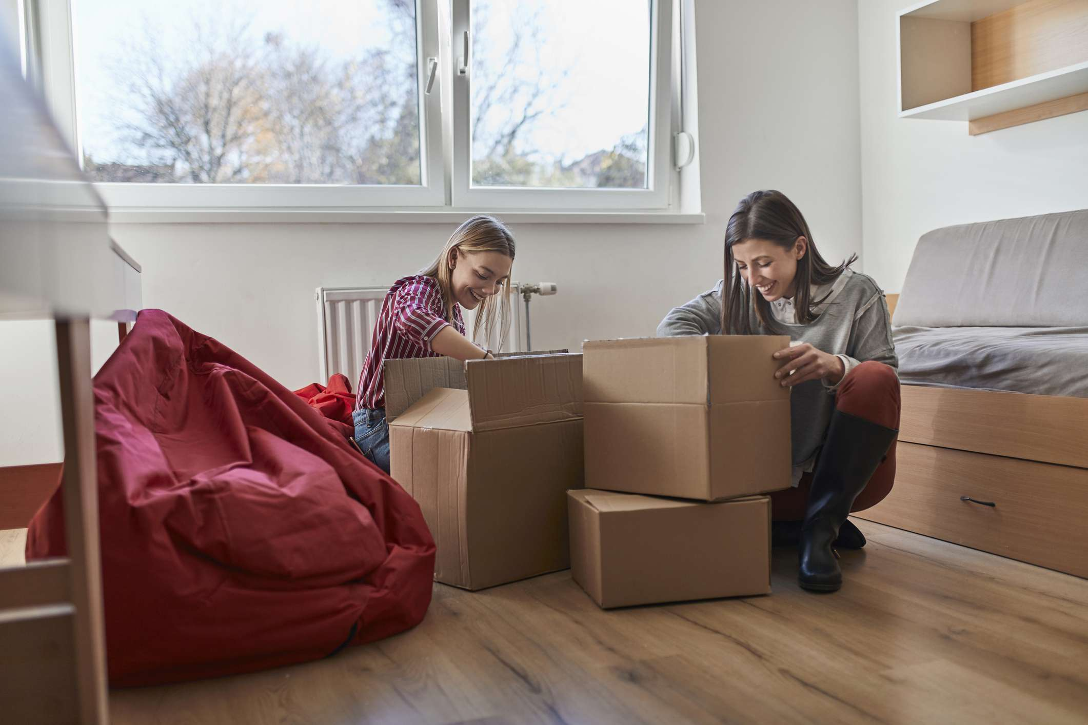 Two young women unpacking cardboard boxes in a room