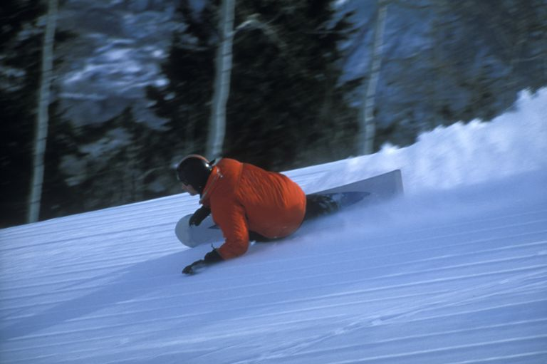 Snowboarder carving turns