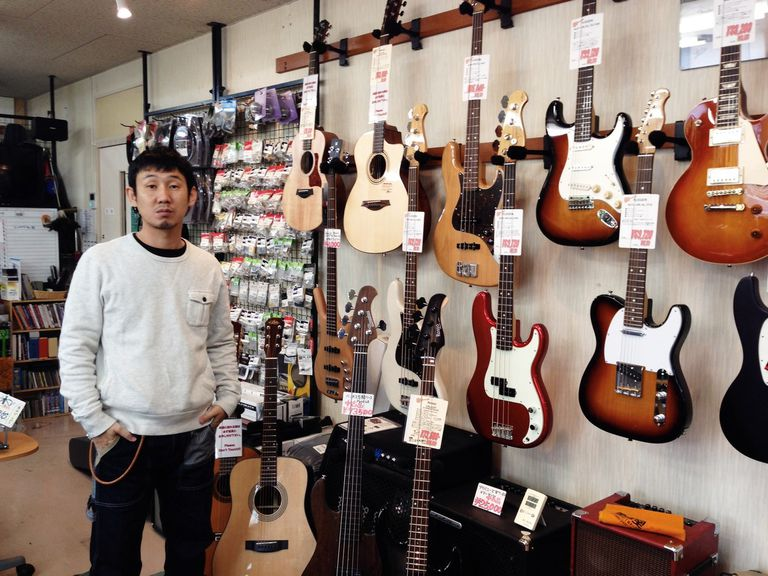 Owner of a music store standing in front of his guitar collection