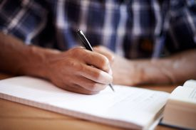 man writing on piece of paper
