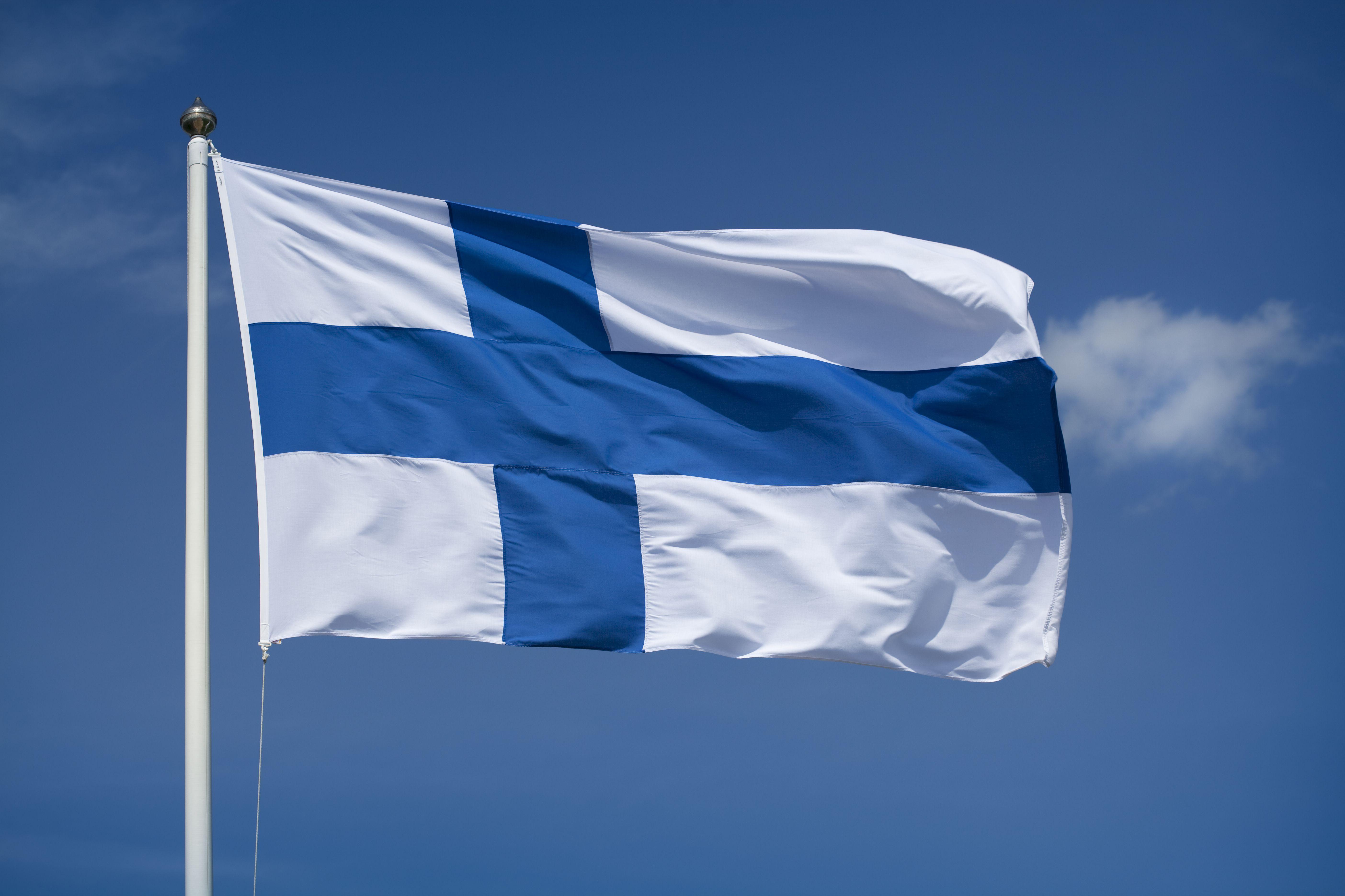 Hoisted Finnish flag with a blue sky background
