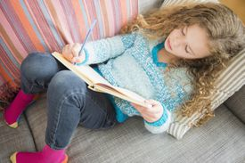 Girl (10-11) lying on sofa and writing in notebook