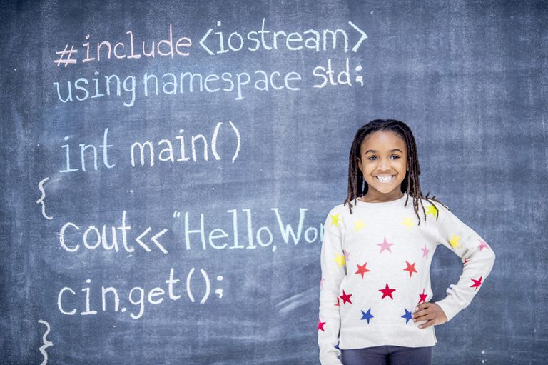 A girl is taking a programming class in her elementary school. She is standing in front of a blackboard that she has written code on.
