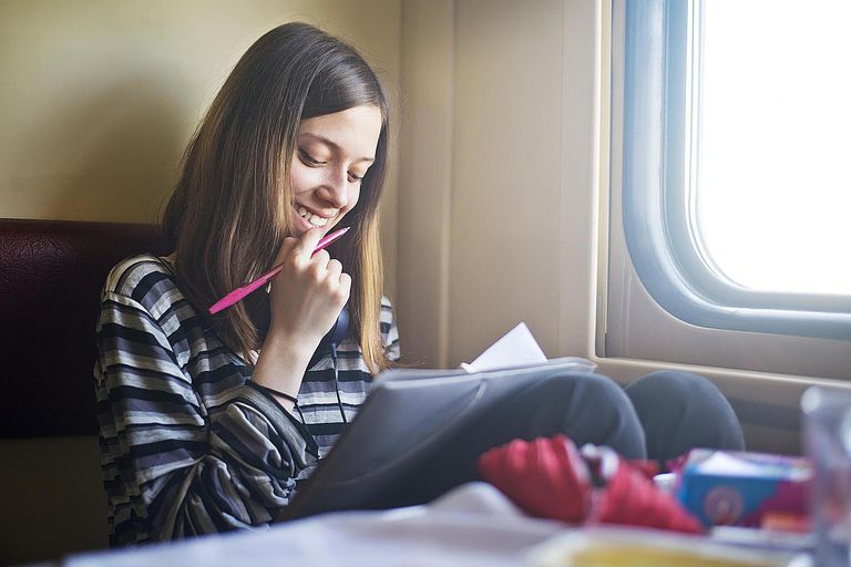 Young Woman Smiling and Writing in a Notebook