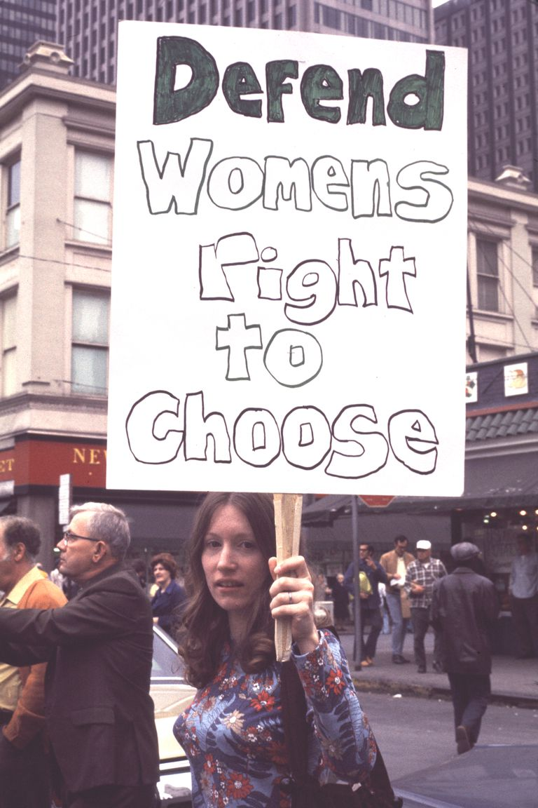 A picture of a women holding a sign in favor of the right to choose.