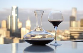 Wine decanter and glass sitting on a table with a city skyline in the background.