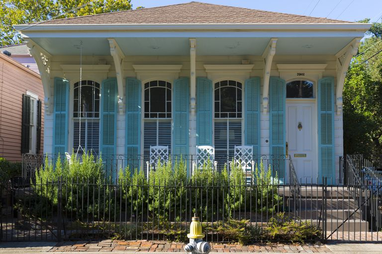 detail facade of New Orleans cottage, overhanging hip roof, bright turquoise shutters and trim on white siding and front door