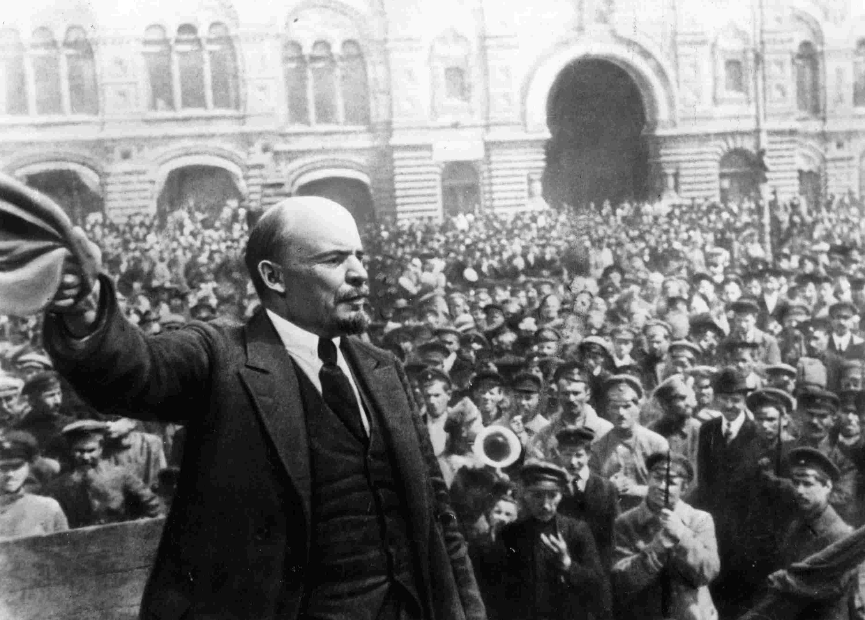 Vladimir Ilyich Lenin holding a hat in front of a large crowd.