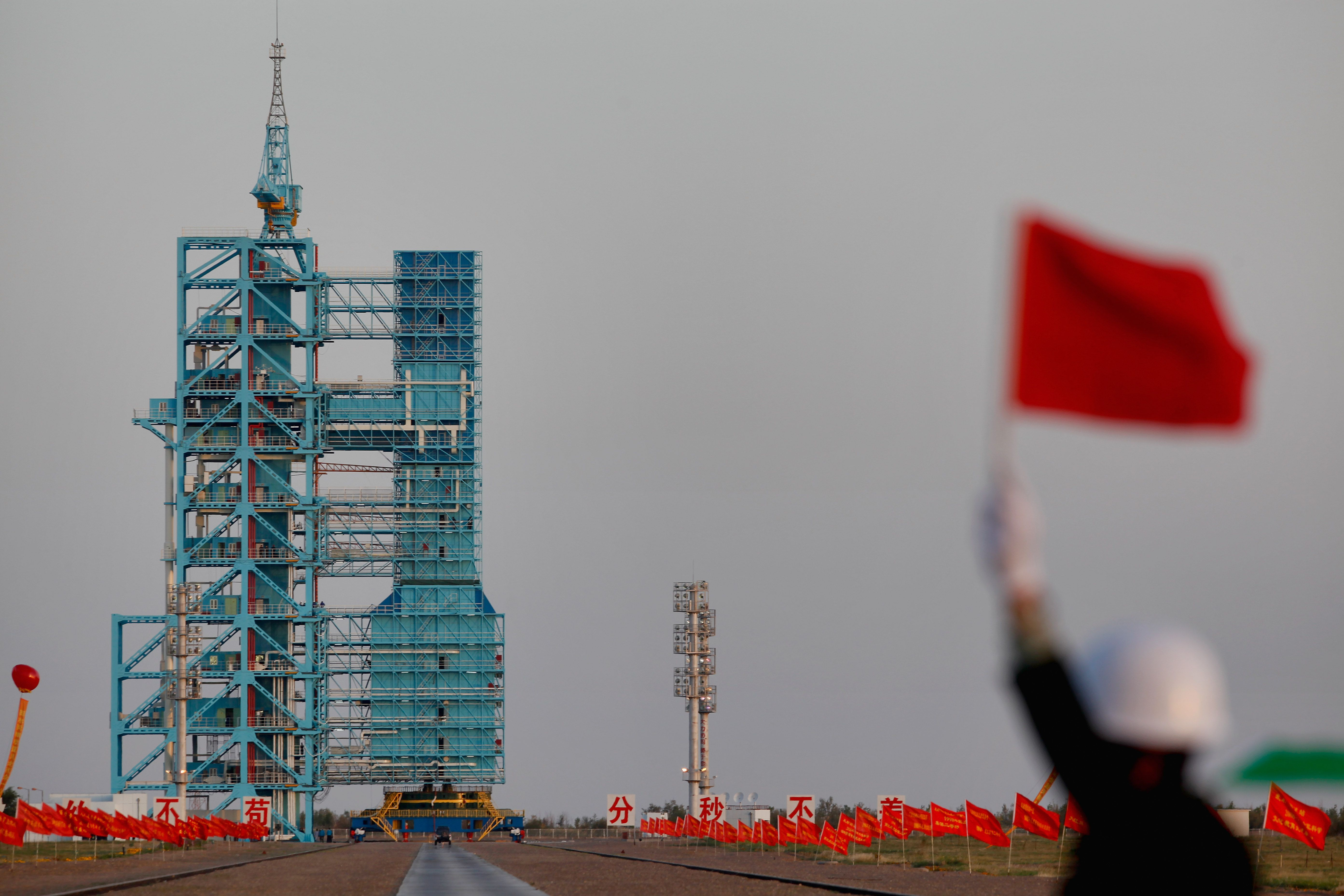 Tiangong-1 prepares for liftoff as a worker waves a red flag.