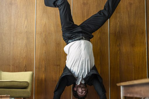 Caucasian businessman doing handstand