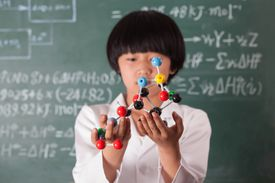 Young Asian holding a model standing in front of a chalkboard.