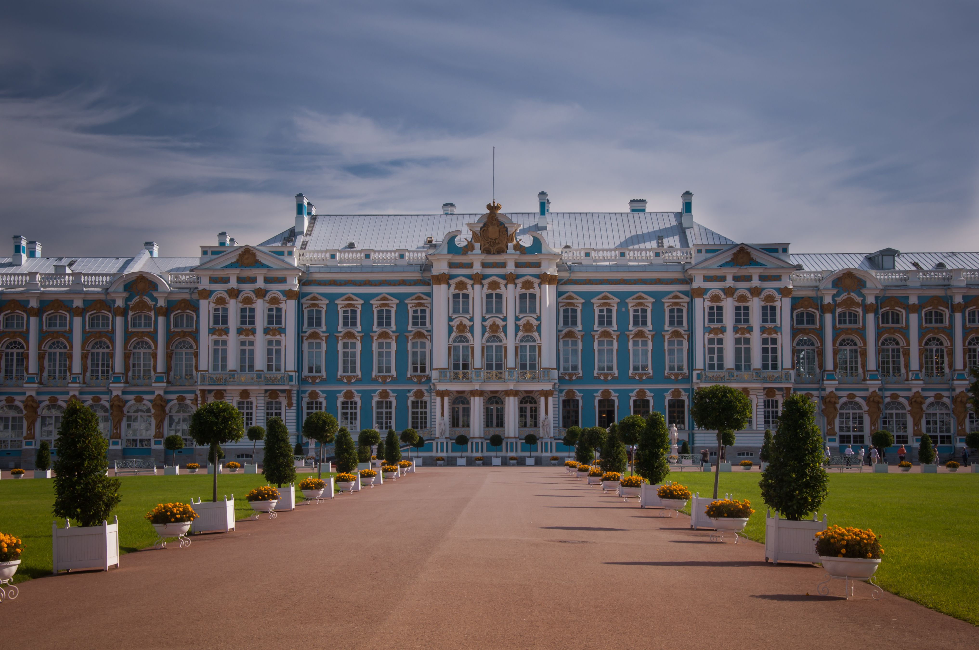 ornate palace, horizontal orientation, blue facade, wide roadway leading to columned entry