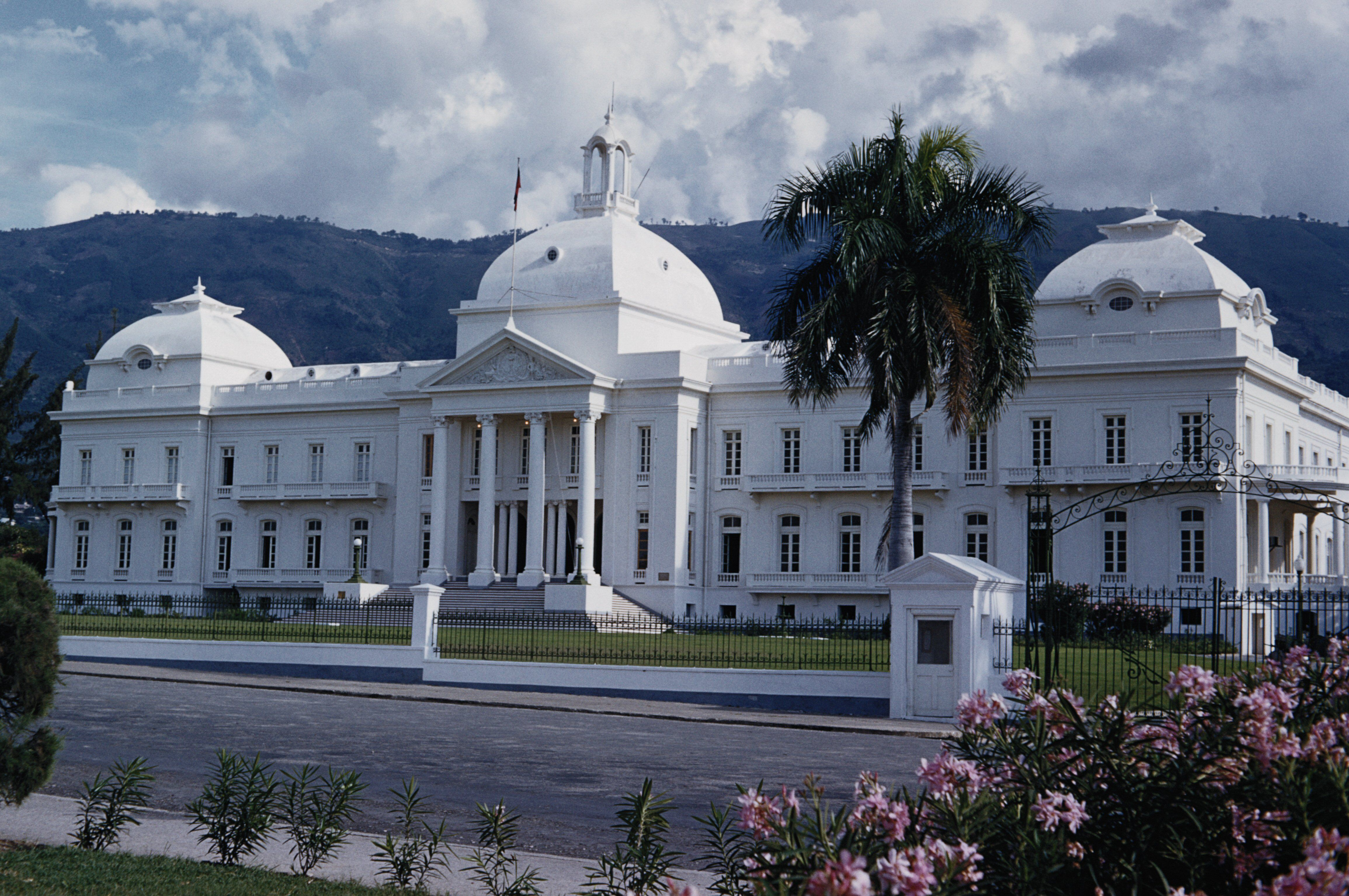 white-colored palace with three domes, symmetrical, center portico with pediment and columns
