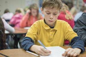 Student writing at desk in classroom