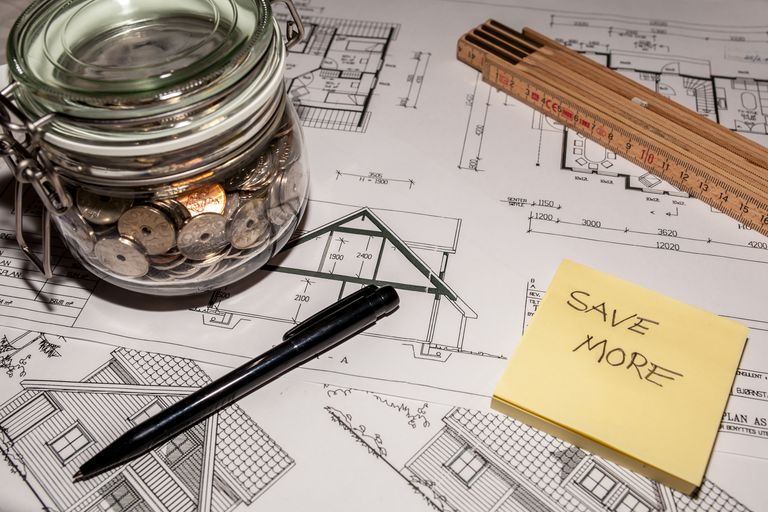 Money jar, pen, extension wood ruler, and Save More written on sticky note - all atop blueprints