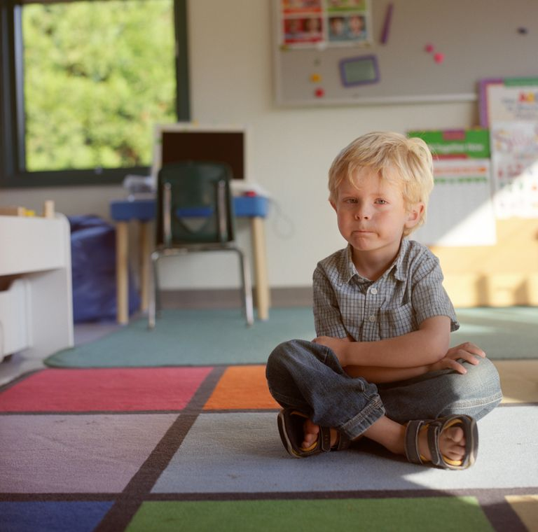 child pouting on the floor of a classroom