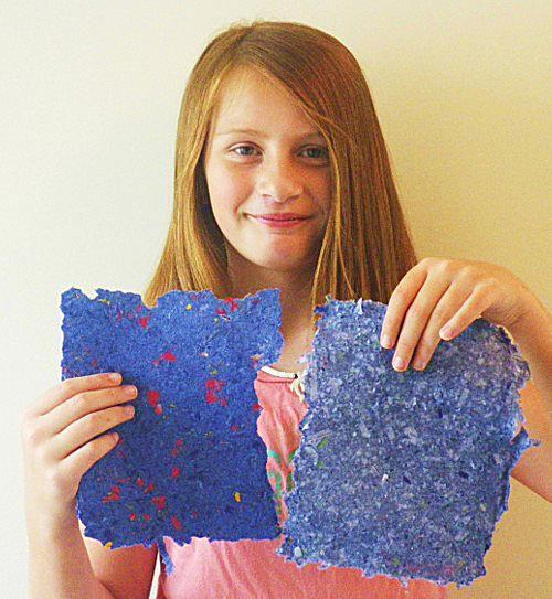 Child holding up handmade paper