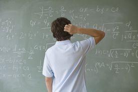 Teenaged boy looking at math equations on a blackboard