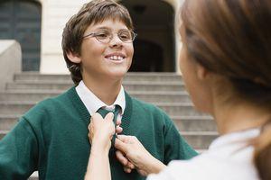 Mom adjusting son's uniform tie