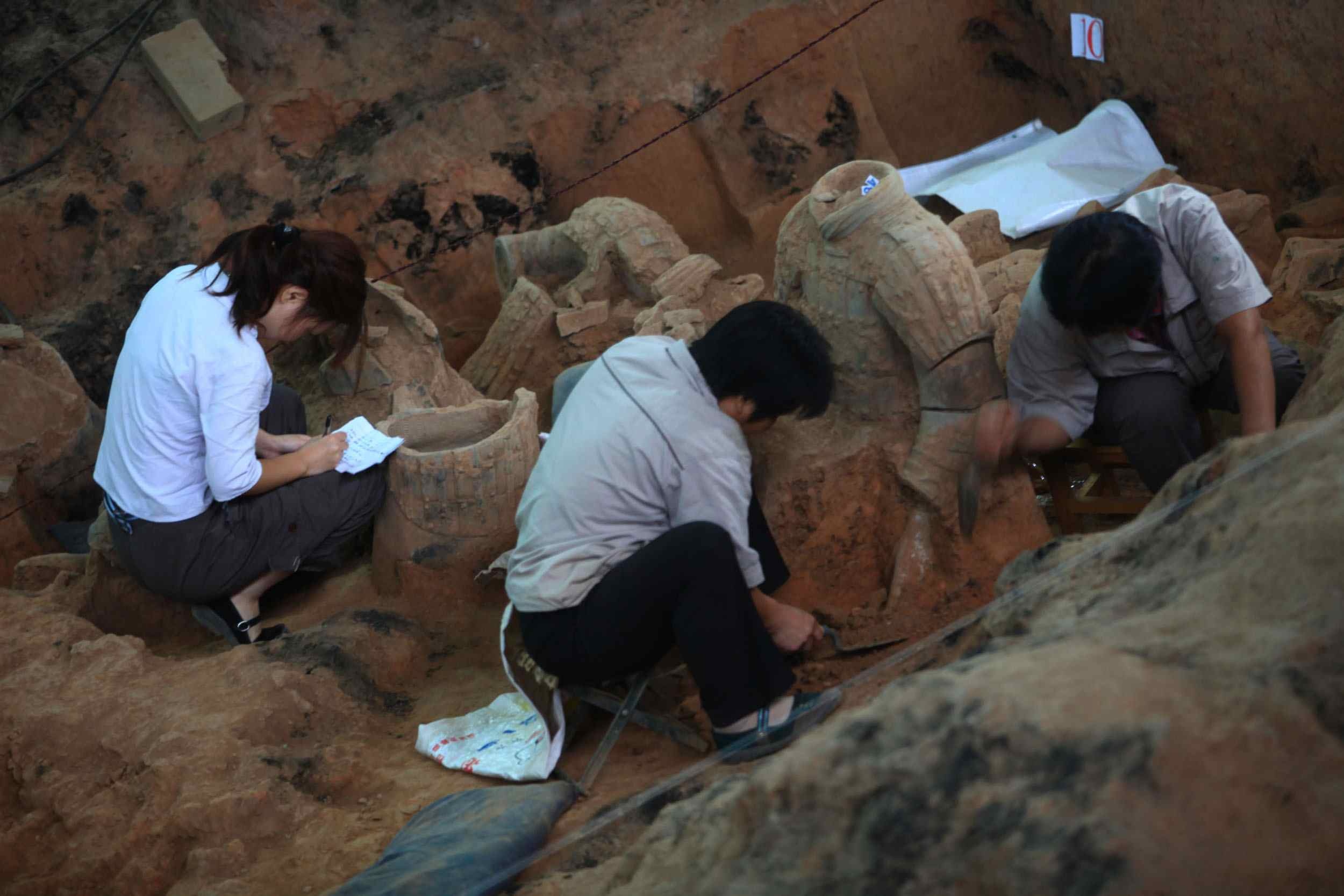 Archaeologists work at the excavation site of No. 1 pit of the Qin Shihuang Terracotta Warriors and Horses Museum in Lintong District of Xian, Shaanxi Province, China. (August 2009)