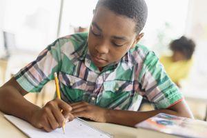 A boy writing on a notepad