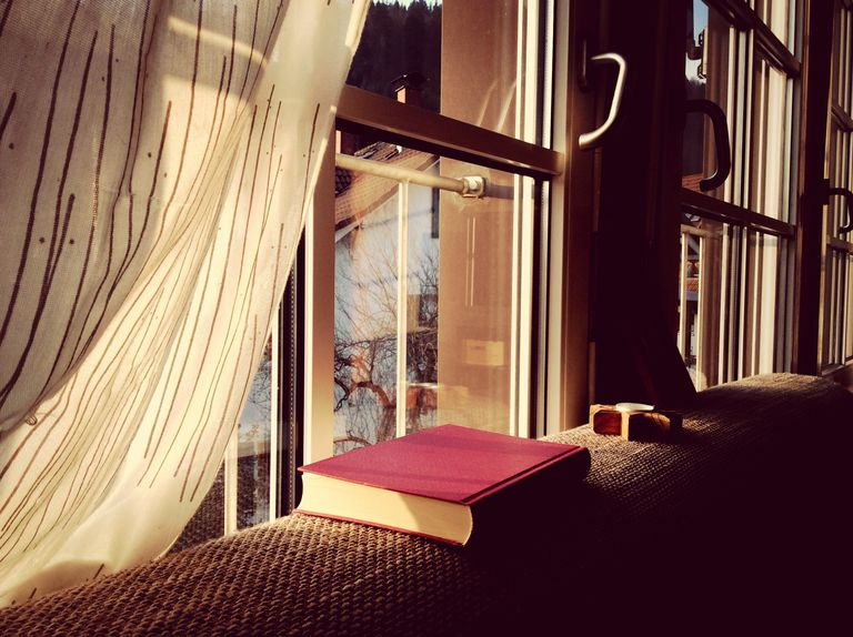 A hardcover book gathering dust on a windowsill