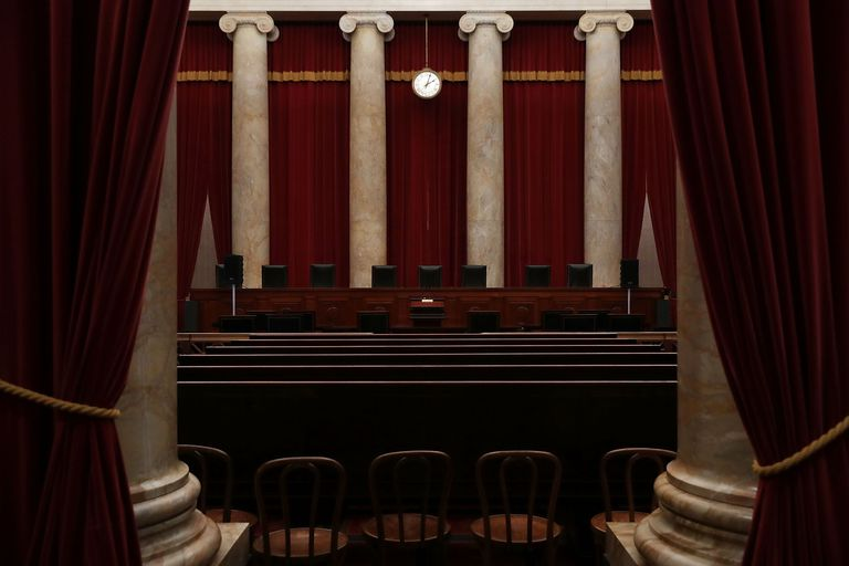 The chambers of the U.S. Supreme Court includes deep red curtains and pale marble columns ine classic style