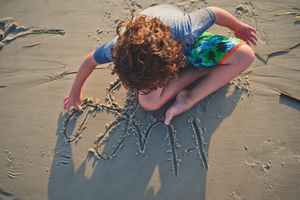 Boy writing in the sand at the beach.
