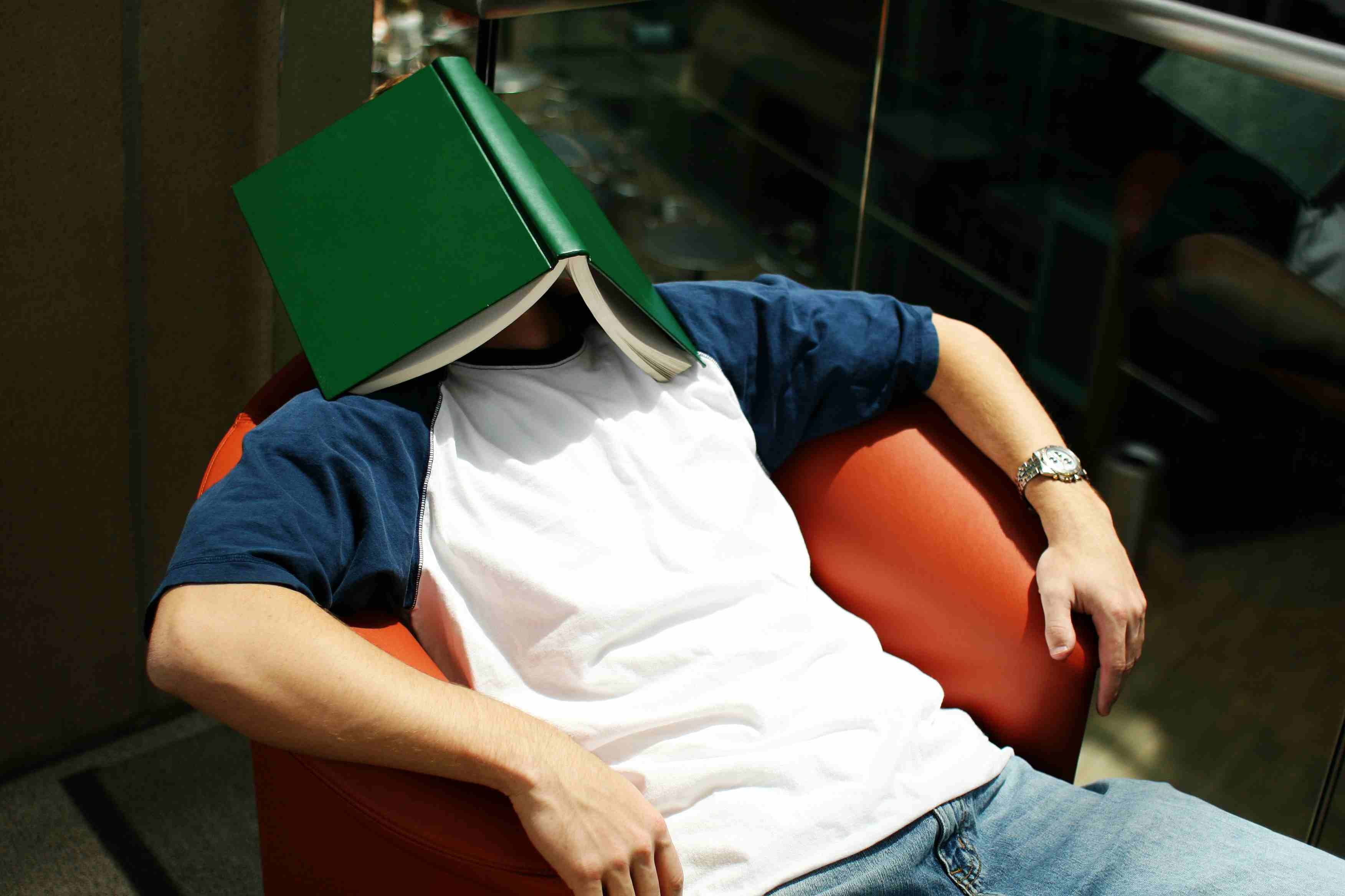 Exhausted student with book on his head