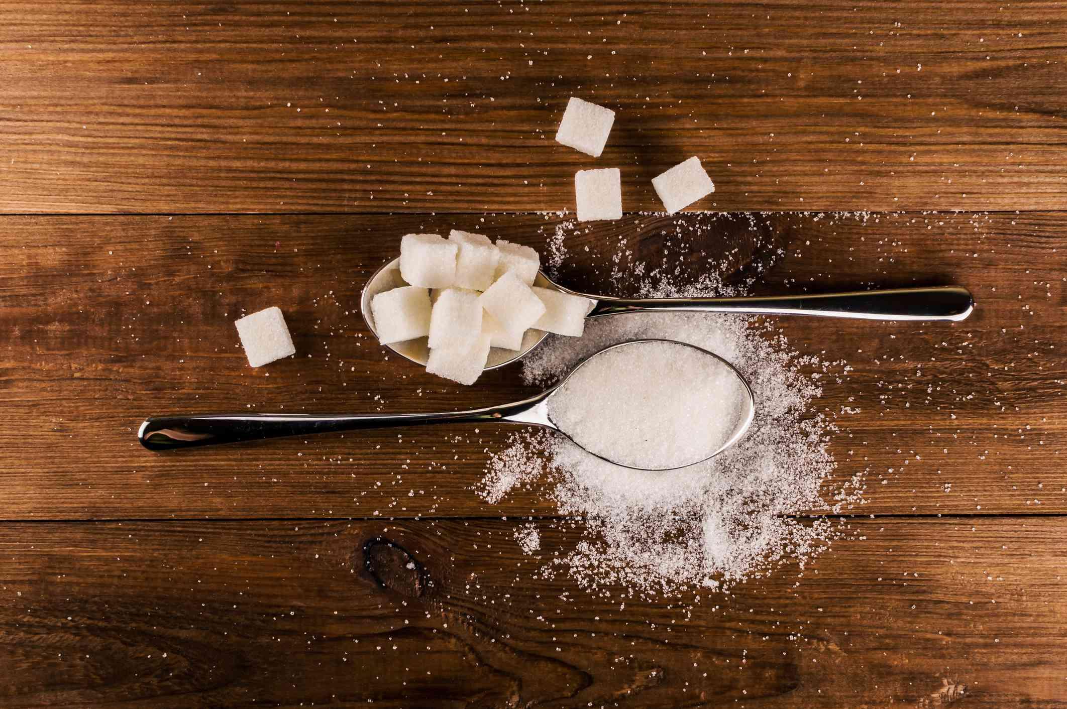 Spoons full of sugar cubes and powder sugar