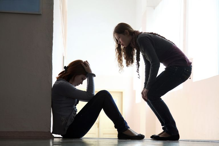 Young woman checking on another sad young woman sitting on floor with head in hands