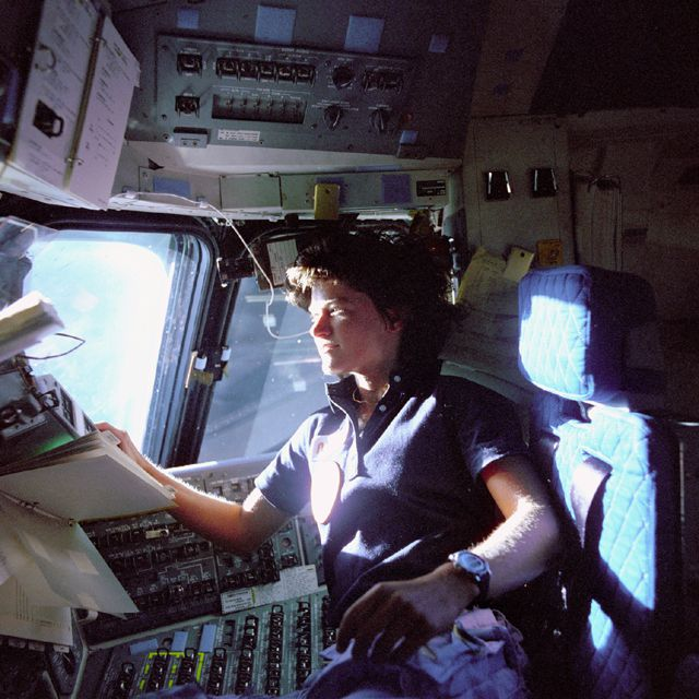 Astronaut Sally Ride in pilot's chair on the flight deck.