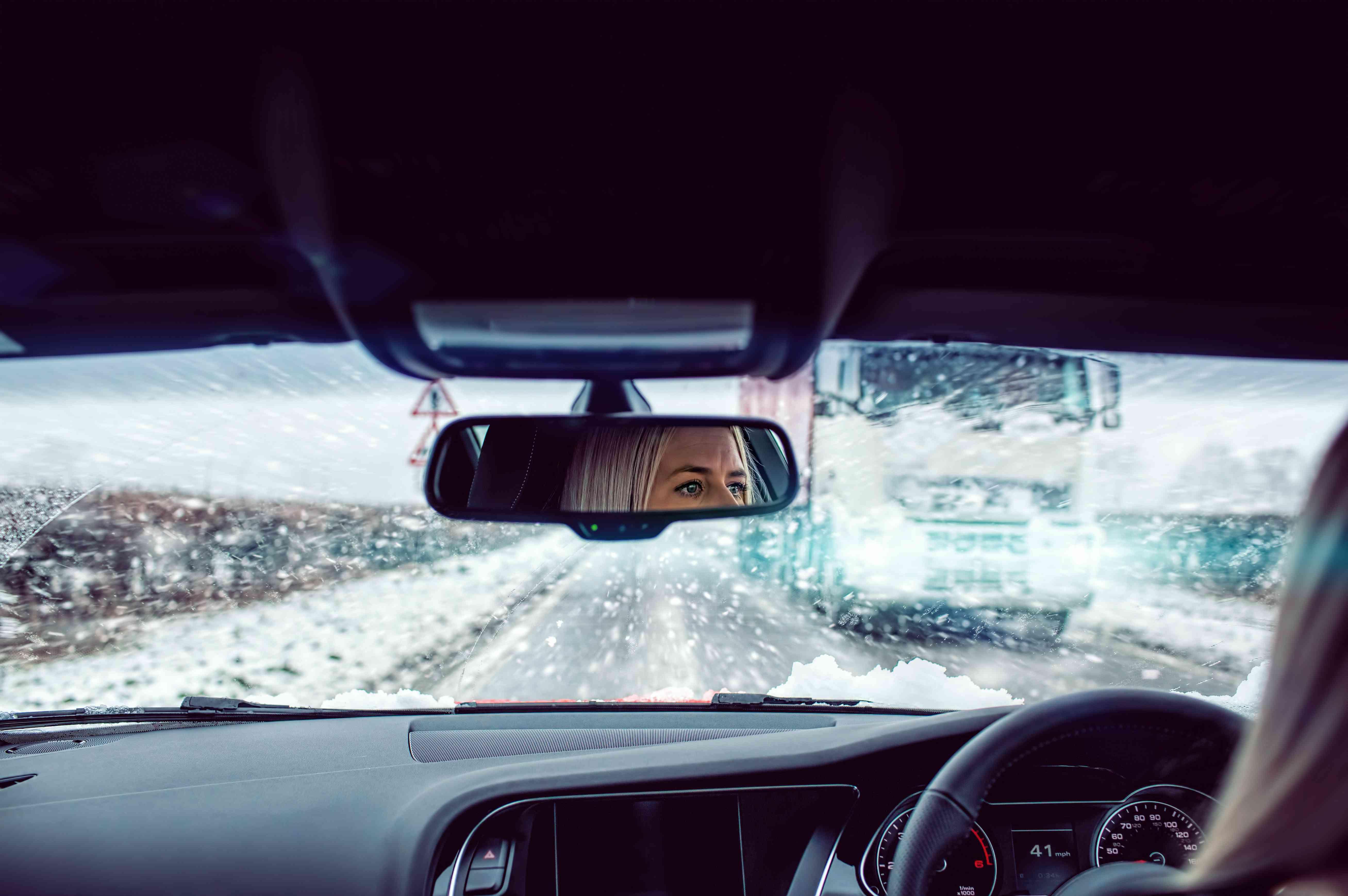 Γυναίκα οδήγηση αυτοκινήτου στο χιονόνερο
