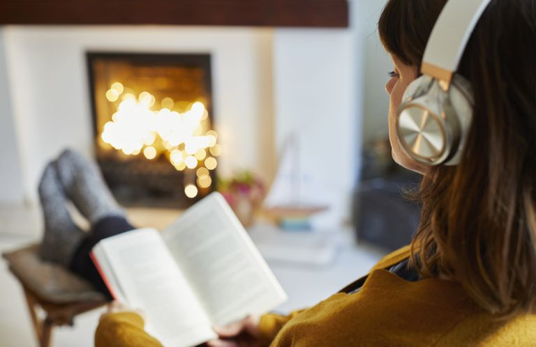 Woman with headphones reading in living room