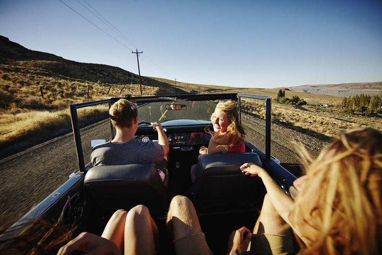 Laughing friends driving in vehicle on desert road