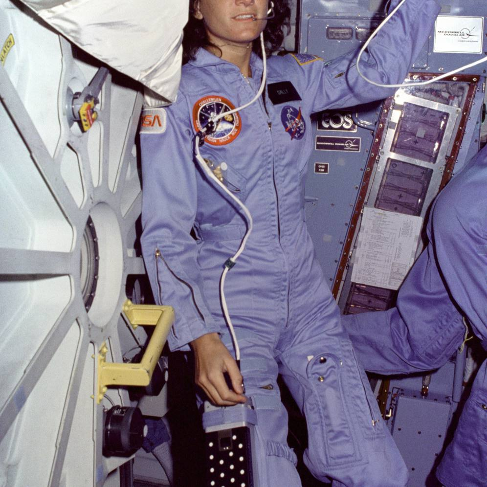 On Challenger's middeck, Mission Specialist Sally Ride floats alongside the middeck airlock hatch.